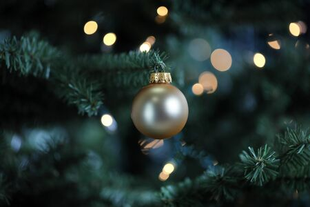 Traditional artificial Christmas tree with gold ball ornament and white lights glowing in background
