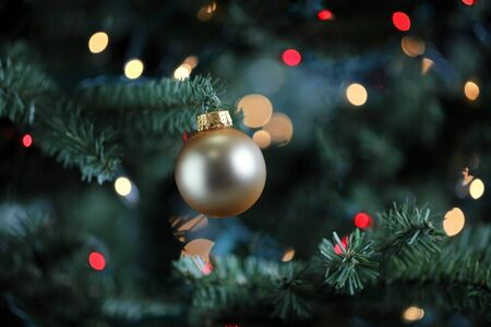 Traditional artificial Christmas tree with gold ball ornament and glowing colorful lights in background