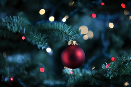 Traditional artificial Christmas tree with red ball ornament and glowing colorful lights in background