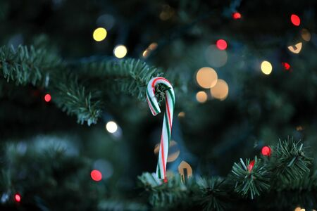 Traditional artificial Christmas tree with candy cane ornament and glowing lights in background