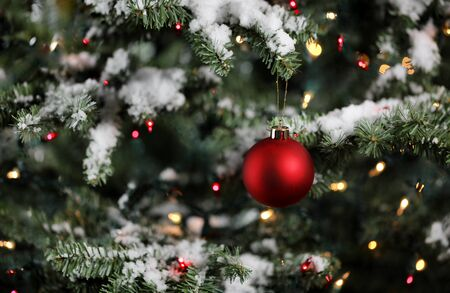 Christmas ornament with snowy fir branches and glowing lights. Winter decoration background.