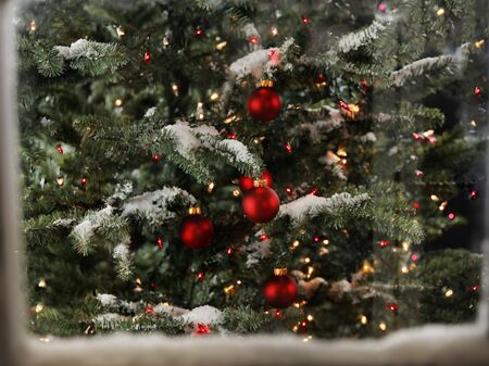 Snow covered window with view of glowing Christmas tree in background 스톡 콘텐츠
