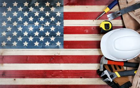 Labor Day concept with tools over distressed wooden United States Flag