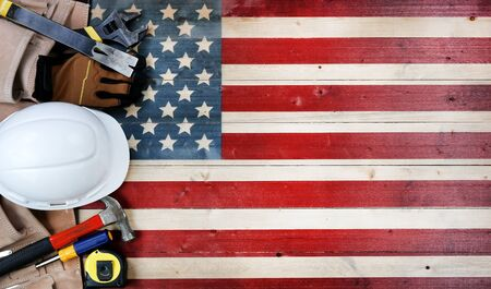 Labor Day concept with worker tools over distressed wooden United States Flag
