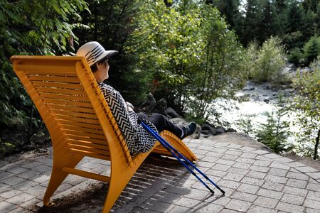 Portrait of senior woman relaxing outdoors in chair after hiking Stock Photo