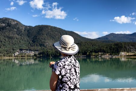 Portrait of senior woman looking out to lake with back to camera