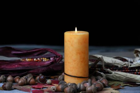 Burning candle for Thanksgiving or Halloween holiday with dark background