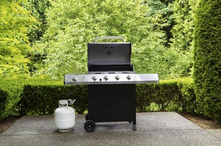 large barbeque cooker, with lid up, on concrete outdoor patio with woods in background