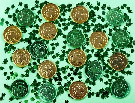 Saint Patricks Day with shamrocks and shiny coins on green background in filled frame format