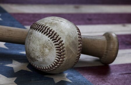 Closeup view of an old baseball and traditional wood bat on rustic wooden United States Flag 版權商用圖片
