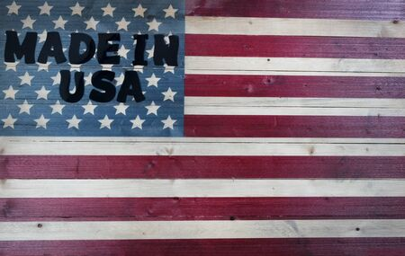 Large text letters spelling Made in USA on vintage wooden United States flag