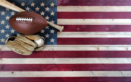 American baseball and football equipment on vintage wooden US flag background. USA sports concept with copy space