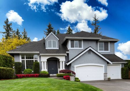 Clean home exterior during springtime with blooming flowers and healthy green grass