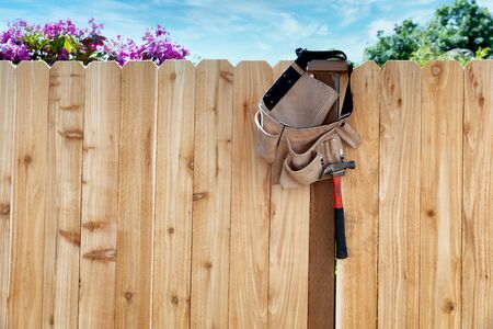 New wooden fence with tool belt and pouch hanging from post