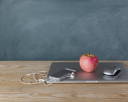 Back to school concept with basic modern technology on desktop with chalkboard in background