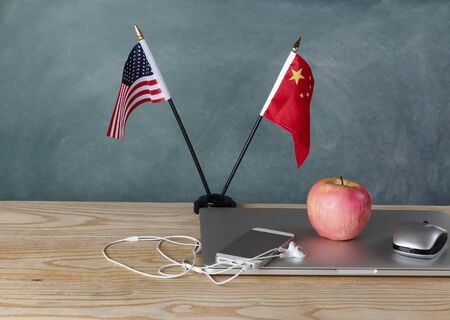 National flags representing China and the United States of America on classroom desk for trade war education concept. Banco de Imagens
