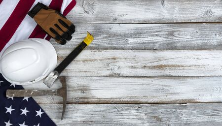 US Happy Labor Day concept with national flag and industrial work tools on white rustic wooden background