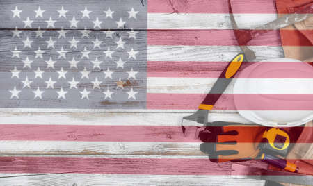 Labor Day concept with industrial worker tools over distressed white wooden boards with see through US Flag