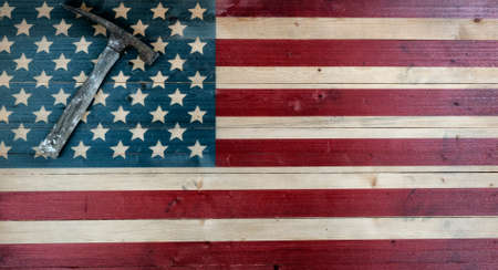 Vintage construction hammer on rustic wooden US flag background with copy space