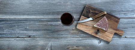 Fresh cheese wedge on cutting board with red wine in a glass on rustic wooden table