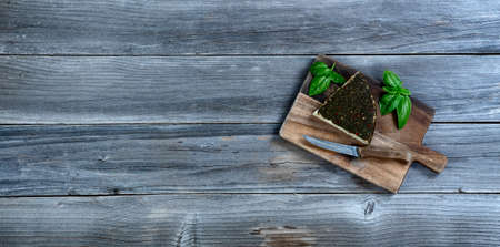 Fresh cheese wedge with basil leaves on rustic wood with copy space available