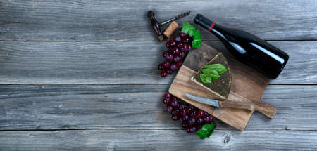 Fresh cheese wedge with a bottle of red wine plus basil leaves and grapes on rustic wood with copy space available