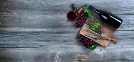 Red wine with fresh cheese wedge plus basil leaves and grapes on rustic wood with copy space available