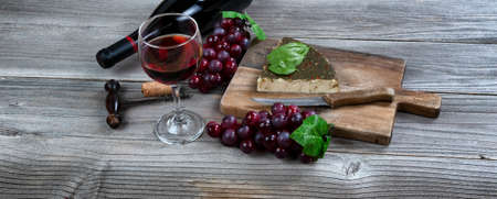 Glass of red wine with fresh cheese wedge plus basil leaves and grapes on rustic wooden table