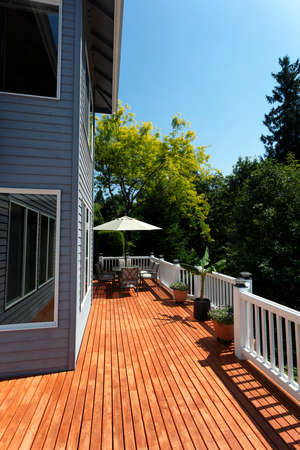 Outdoor home wooden cedar deck patio during lovely summer day with seasonal garden in vertical layout Banco de Imagens