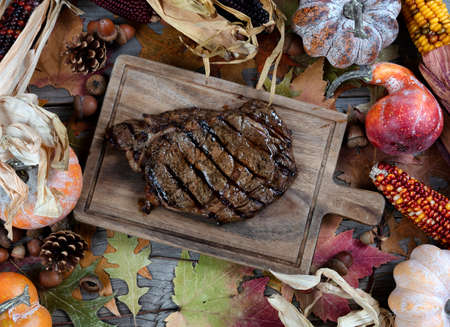 Freshly grilled steak with seasonal autumn decorations on table Banco de Imagens