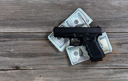 Hand gun on top of cash pile for business concept 版權商用圖片
