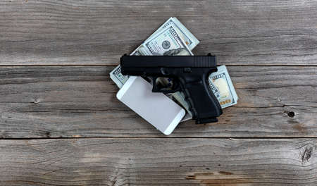 Hand gun and cell phone on top of cash pile for business concept Banco de Imagens