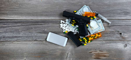 Drug business concept with weapon and cell phone on top of cash pile Banco de Imagens
