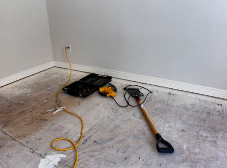Renovation of home floor with exposed plywood and tools for preparation of hardwood