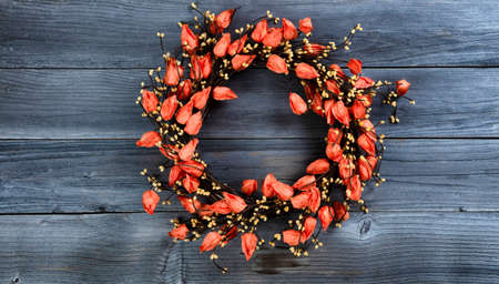 Seasonal autumn wreath with orange bell flowers on vintage wooden background