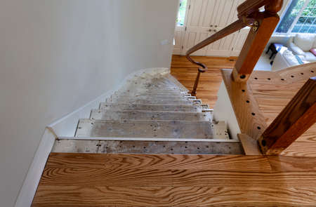 Renovation of home staircase with exposed plywood and new red oak wooden floor boards
