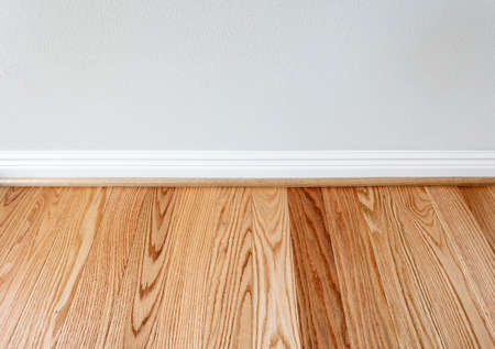 Newly installed red oak floor boards with trim protection for wall