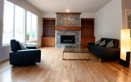 Family room remodeled with solid red oak wooden floors and new furniture. Gas insert fireplace operating in background.