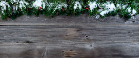 Merry Christmas concept on rustic natural wooden background with snow covered Fir branches with plenty of copy space