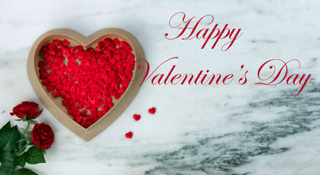 Happy Valentines Day with lovely red rose flowers plus large heart shaped giftbox filled with small hearts on natural marble stone background plus text message