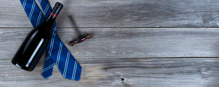 Blue striped necktie and a bottle of red wine and corkscrew opener on weathered wooden planks for Happy Fathers Day concept