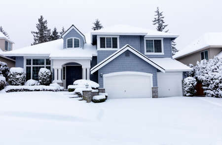 Curbside view of residential home during winter snowstorm with visual light snow coming down