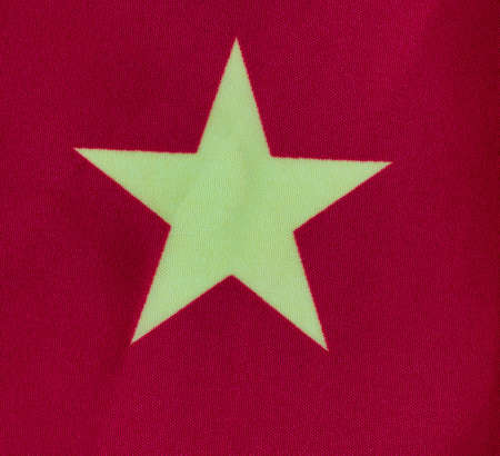 Single yellow star on red cloth background for national China symbol in close up format