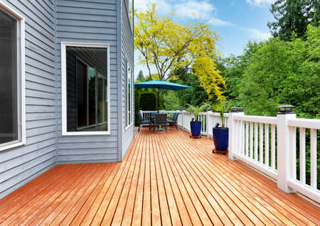 Home outdoor wooden cedar deck with patio furniture and decoration palm plants Banco de Imagens