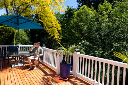 Mature man on home outdoor deck drinking a beer out of glass while sitting in patio furniture chair Banco de Imagens
