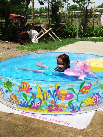 kiddie: A child playing in a kiddie pool one summer day