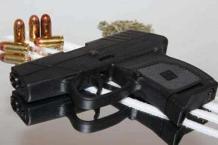 Handgun, bullets, white lines, and drugs isolated on mirrored background Stock Photo