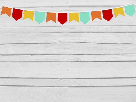 string top: Brazilian june party, festa junina mockup. Birthday or baby shower mockup scene. String of paper flags. Party decoration. White wooden background, empty space. Top view.