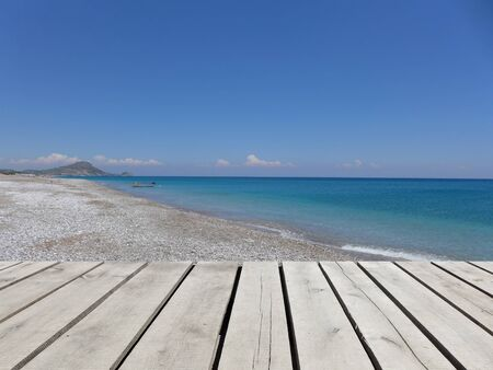 white pebble: Wooden pier with blue sea, sky and white pebble beach background. Mediterranean landscape in sunny day. Greek island. Vacation concept. Afandou beach, Rhodos, Greece, Europe. Scenic view.