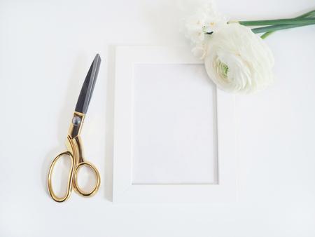 Gestileerde stockfoto. Vrouwelijk productmodel met bos van boterbloem, Ranunculus en gele narcisbloemen, leeg wit kader en gouden schaar op witte achtergrond. Plat leggen, bovenaanzicht. Stockfoto